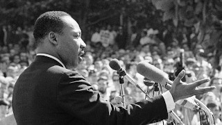 Dr. Martin Luther King Jr. addressing a large crowd.