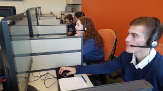 Students sitting at computers for sports polling