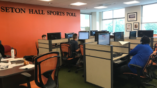Students at computers with headsets on calling to interview people for Sports Polling.
