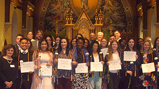 Student standing in chapel with certificates.