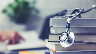 A Stethoscope Draped Over A Stack of Books