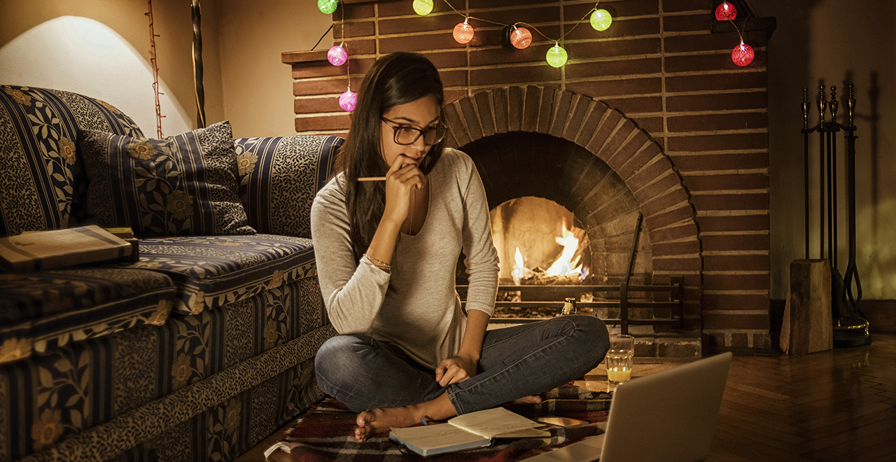 A student sitting in front of her fireplace taking an online course.